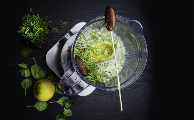 gr?n smoothie Blandning av avokadot, spenat, kiwin, bananen, vetegräs, spirulinaen och kokosnötvatten royaltyfri bild