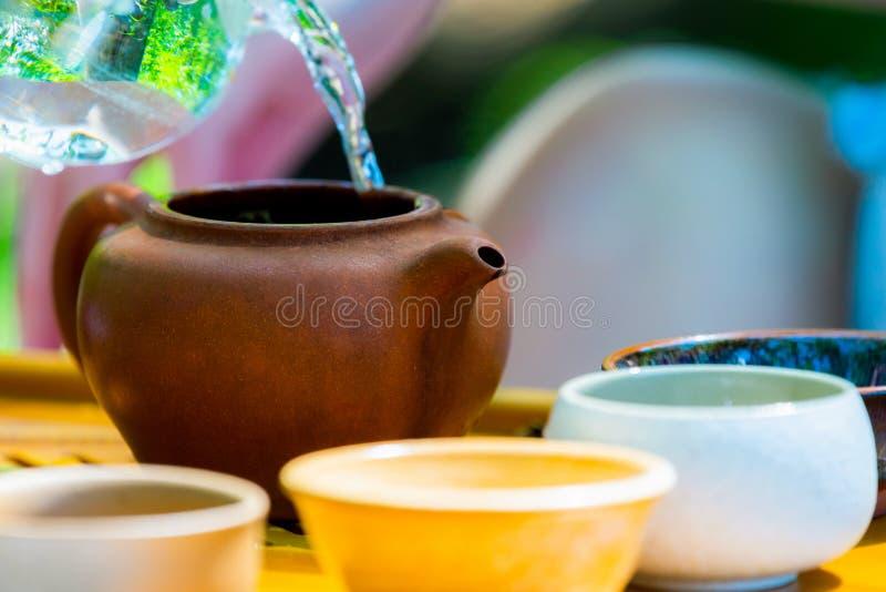 Gr?n tea med koppen och teapoten Tekanna och bunkar med kinesiskt te på en trätabell royaltyfri foto