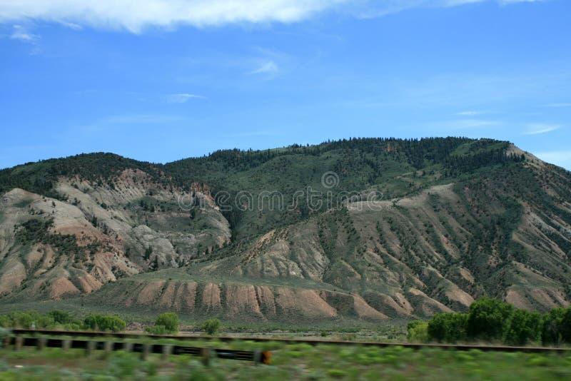 Gr?ne Berge und Schluchten des Staat Colorados Unten gibt es eine Eisenbahn mit einem langen Zug stockbilder