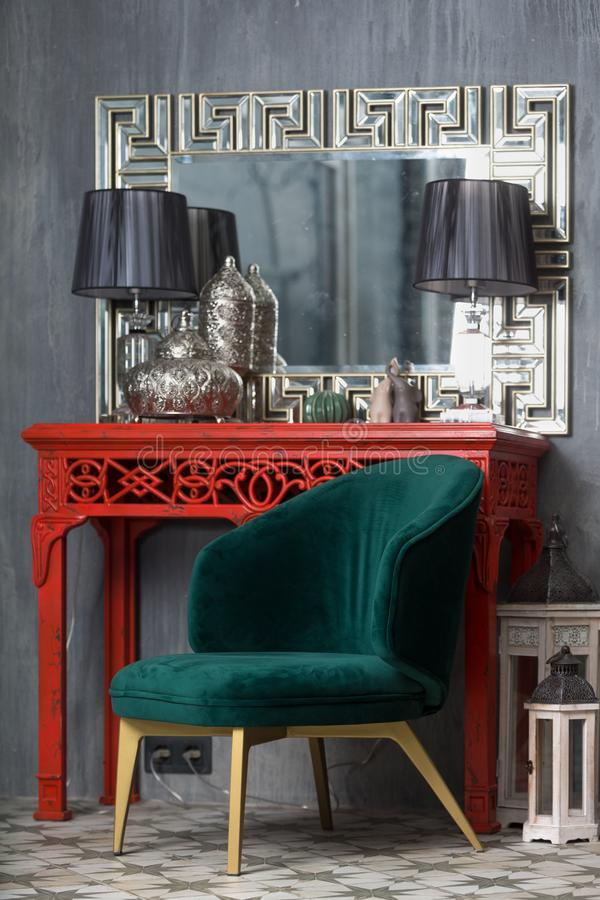 Gr?ner Retro- Stuhl nahe der roten Frisierkommode lizenzfreie stockfotografie