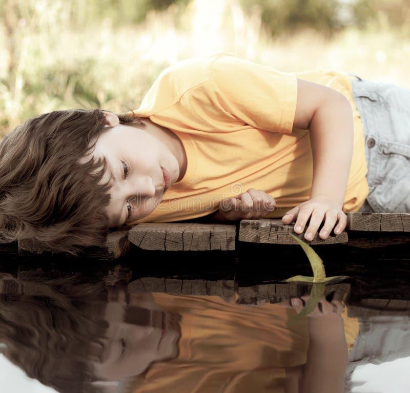 Gr?nes Blattschiff in der Kinderhand im Wasser, Junge im Parkspiel mit Boot im Fluss lizenzfreies stockfoto
