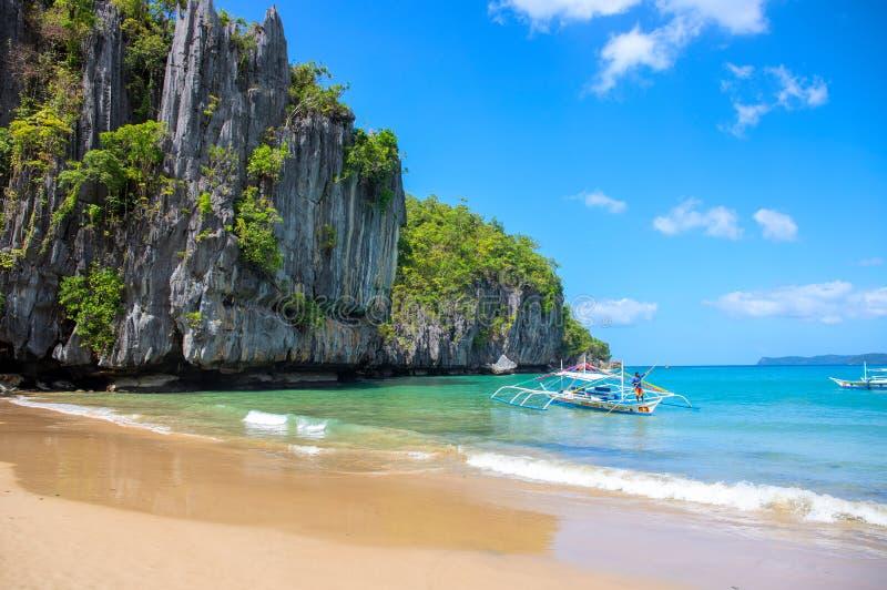 Gr Nido, de Filippijnen - 20 Nov. 2018: Toeristenboot op kust van idyllisch tropisch eiland met zandstrand en blauwe overzees stock foto