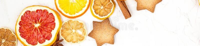 Gr?ns av torkade skivor av olika citrusfrukter pepparkaka och kryddor p? vit bakgrund med copyspace royaltyfri fotografi