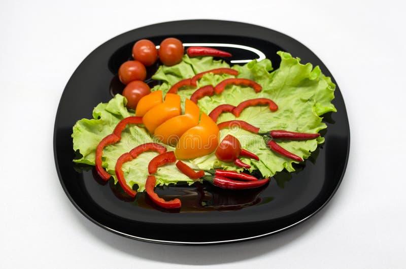 Gr?nsaker p? en platta som l?ggas ut i formen av en skorpion royaltyfri fotografi