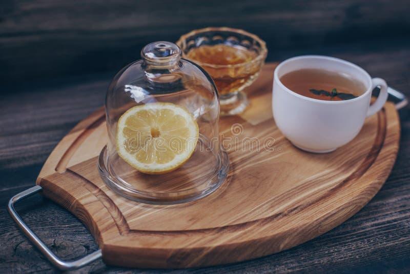 Gr?nt te i den vita koppen, citron under det genomskinliga locket arkivfoto
