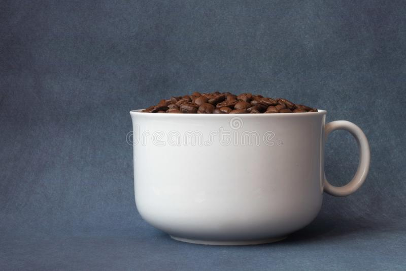 Gr?os de caf? em um copo branco fotos de stock