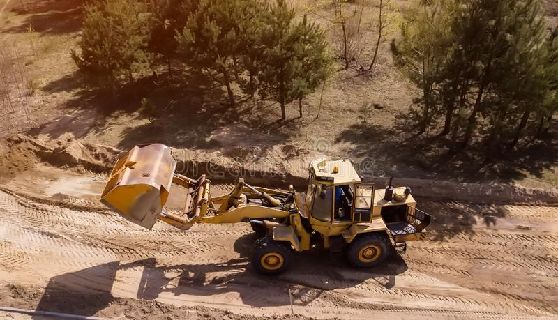 Gr?vskopan laddar sanden in i lastbilen Arbetare g?r v?gen royaltyfri foto