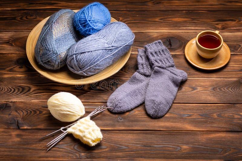 Gr?a woolen stack sockor, stack garner och en kopp te p? ett tefat p? en tr?bakgrund royaltyfri foto