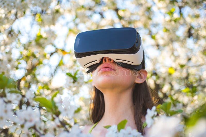 gra jest dalej Wirtualna technologii symulacja Śliczna dziewczyny sztuka w wiosna ogródzie Młodej damy odzieży vr szkła w wiośnie zdjęcia royalty free