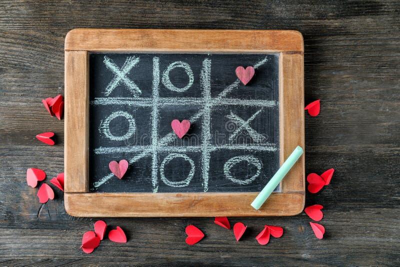 Gra palec u nogi z krzyżującymi kreskowymi i małymi sercami na blackboard, odgórny widok obrazy royalty free
