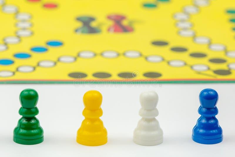 Gra planszowa z różnymi barwionymi gemowymi pionkami na nim Ludo lub Zmartwione gry planszowa sztuki postacie obrazy stock