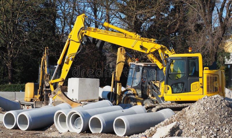 Graaf, minigraafwerktuig en bulldozer in een wegenbouwplaats Pijpenbeton vooraan wordt geprefabriceerd die stock afbeelding