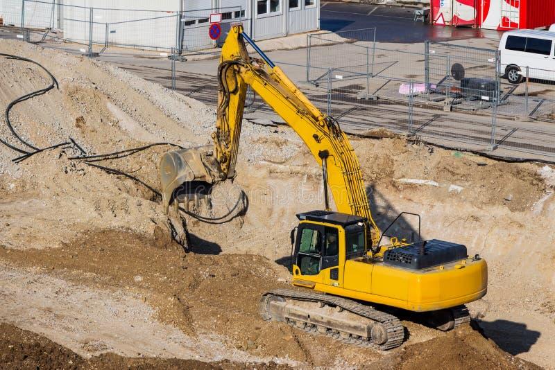 Graafwerktuig bij bouwwerf tijdens uitgraving stock foto's