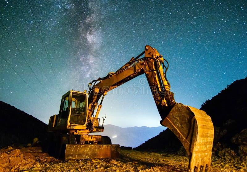 Graafwerktuig bij nacht in een carrière tegen de achtergrond van een nacht sterrige hemel stock foto