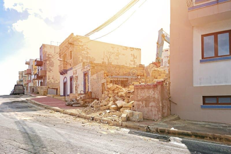 Graafwerktuig die bij de vernieling van een oude woningbouw werken stock fotografie