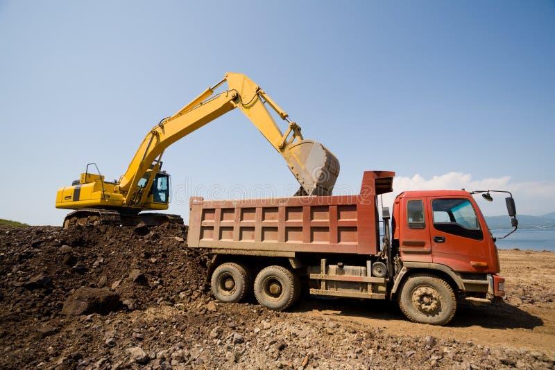 Graafwerktuig en zware stortplaatsvrachtwagen stock fotografie