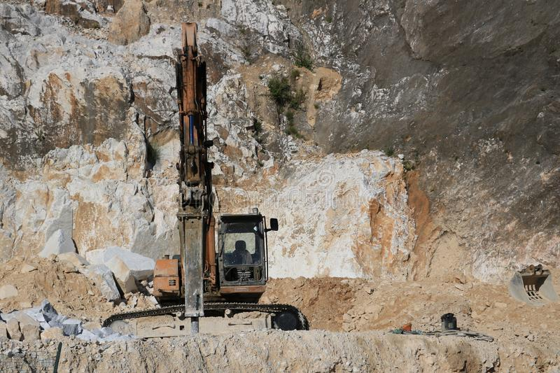 Graafwerktuig met vernielingshamer in een marmeren steengroeve van Carrara L stock afbeeldingen