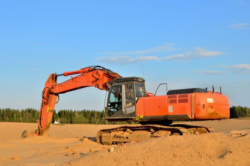 Graafwerktuig op de bovenkant van een open industri?le zandkuil waar mijnbouwverrichtingen stock foto's