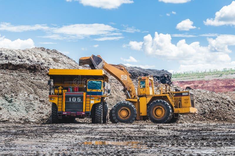 Graafwerktuiglading van steenkool, erts op de stortplaatsvrachtwagen De grote stortplaats t royalty-vrije stock afbeelding