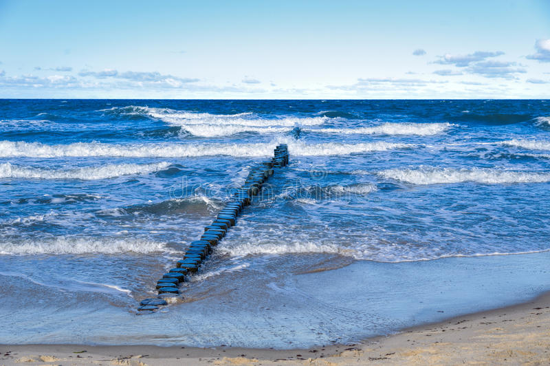 Graal-Muritz. Groynes in the surf on the German Baltic coast royalty free stock images
