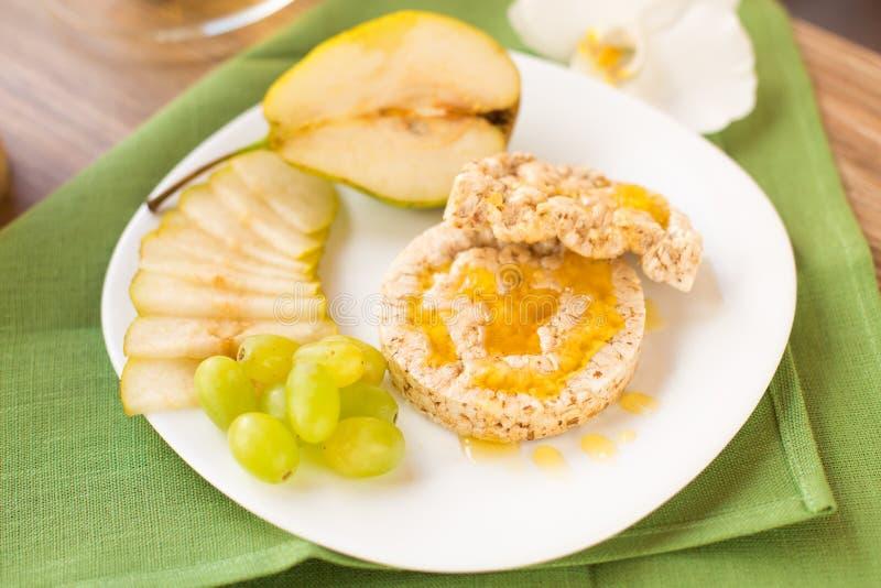 Graancrackers met honing en vruchten stock afbeelding