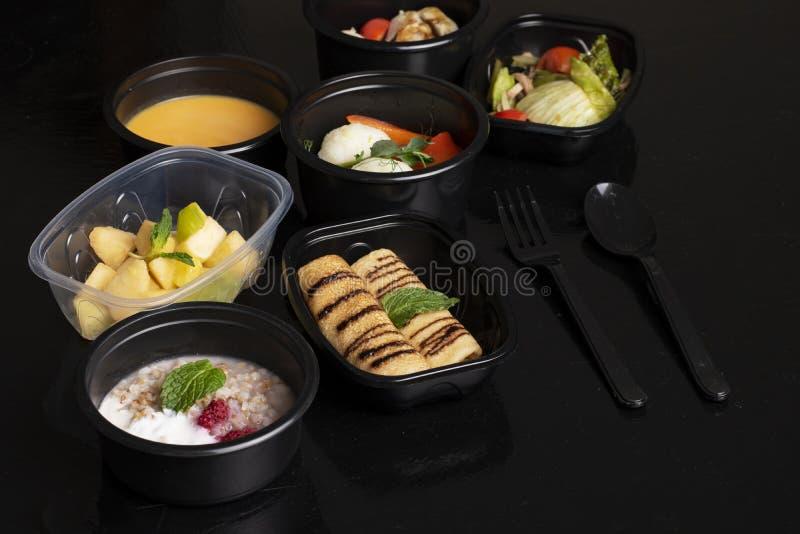 Graangewassen en bessen, pompoensoep met gestoomde groenten, sla en exotische vruchten salade op zwarte lijst royalty-vrije stock foto's