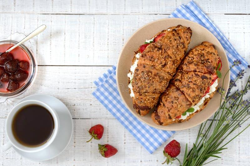 Graangewassencroissants met roomkaas en verse aardbeien, kop thee en jam stock afbeelding