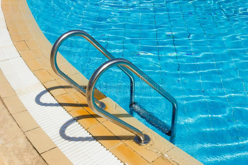Grab bars ladder in the swimming pool stock photography