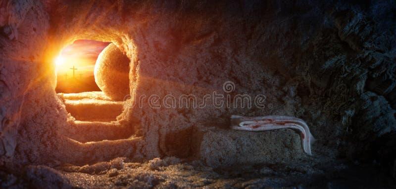 Grab leer mit Leichentuch und Kreuzigung bei Sonnenaufgang lizenzfreie stockbilder