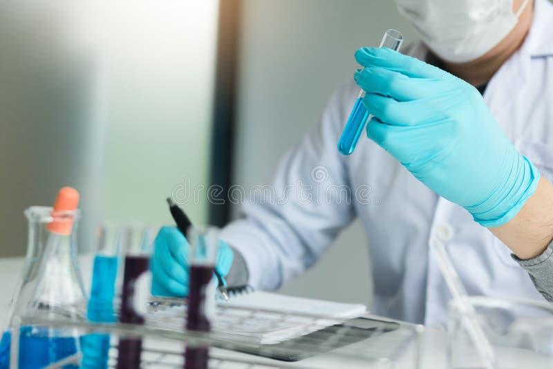 Grabación del científico que hace la nota en el libro con su tubo de ensayo de los hallazgos en laboratorio imágenes de archivo libres de regalías