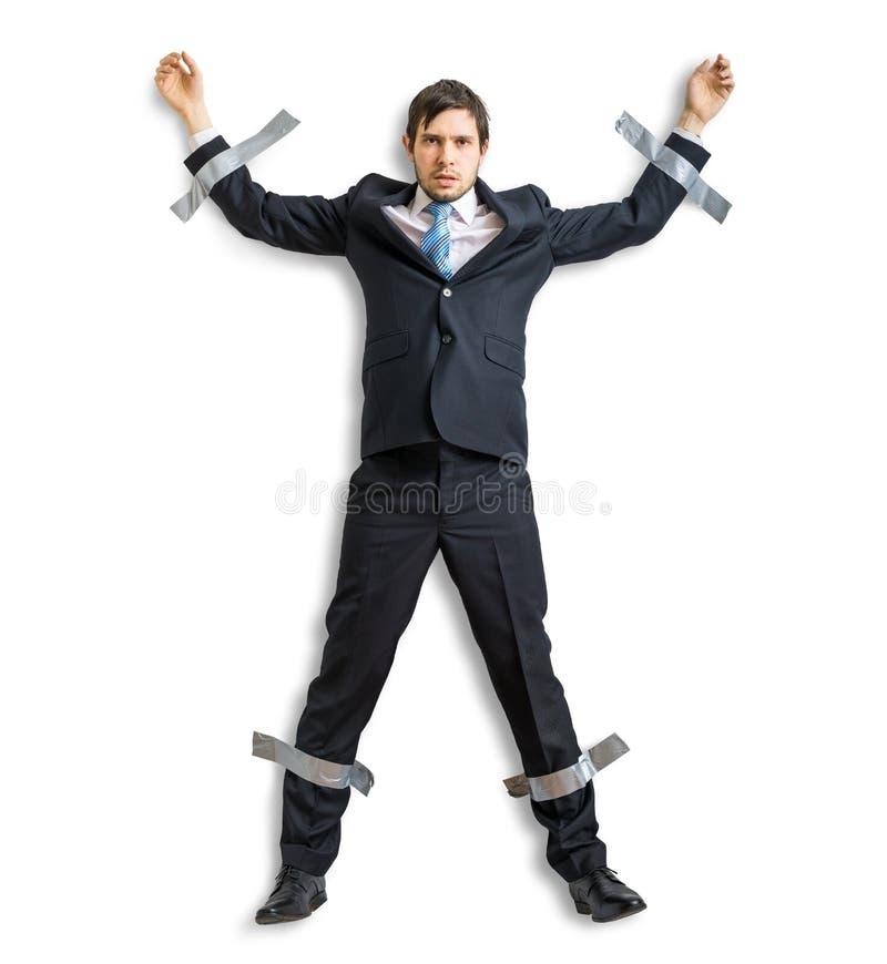 Graban al hombre de negocios en traje a la pared con la cinta adhesiva imagen de archivo