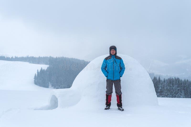 Grabb i bergen nära en snöig igloo royaltyfri foto