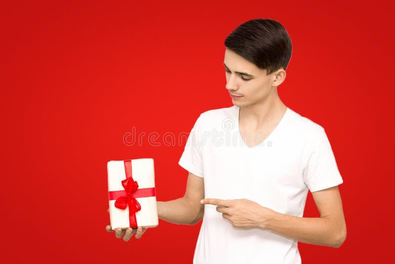 Grabb i en vit T-tröja med en gåva på en röd bakgrund, en att bry sig ung man fotografering för bildbyråer