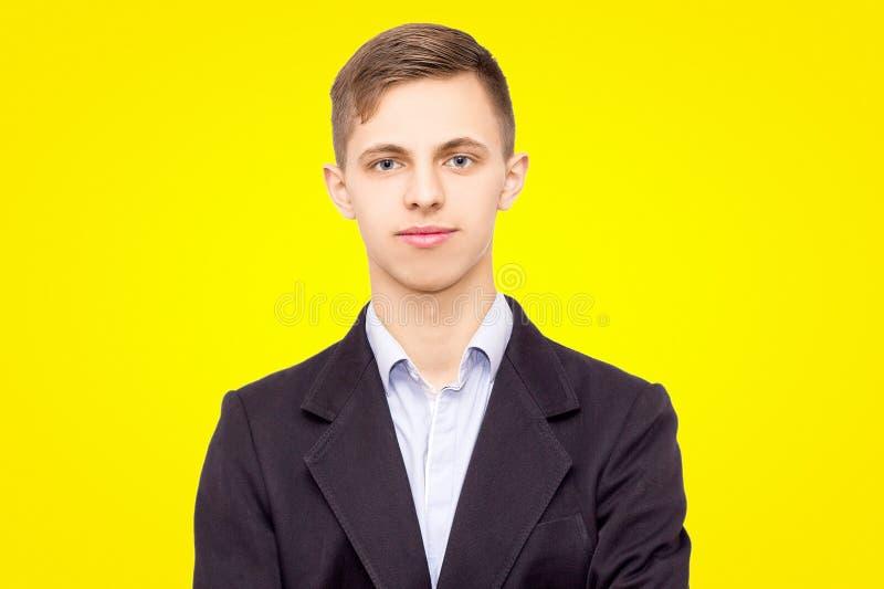 Grabb i ett omslag och en skjorta som isoleras på gul bakgrund, tyst ung man royaltyfria bilder