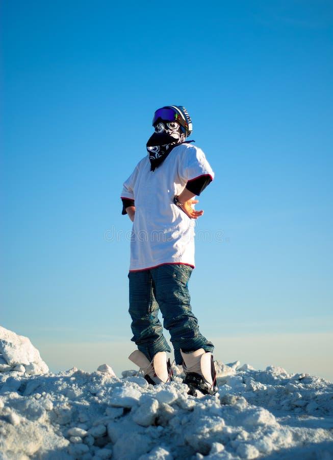 Grabb i snowboardkugghjulanseende på ett berg royaltyfria bilder