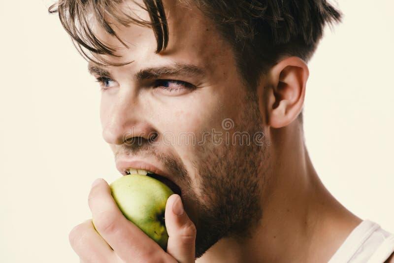 Grabb med den allvarliga framsidan som isoleras på ljus - grå bakgrund, slut upp Mannen med det gröna äpplet i hans hand biter de royaltyfri bild