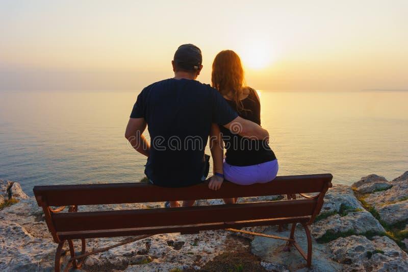 Grabb med en flicka som håller ögonen på solnedgången arkivfoto