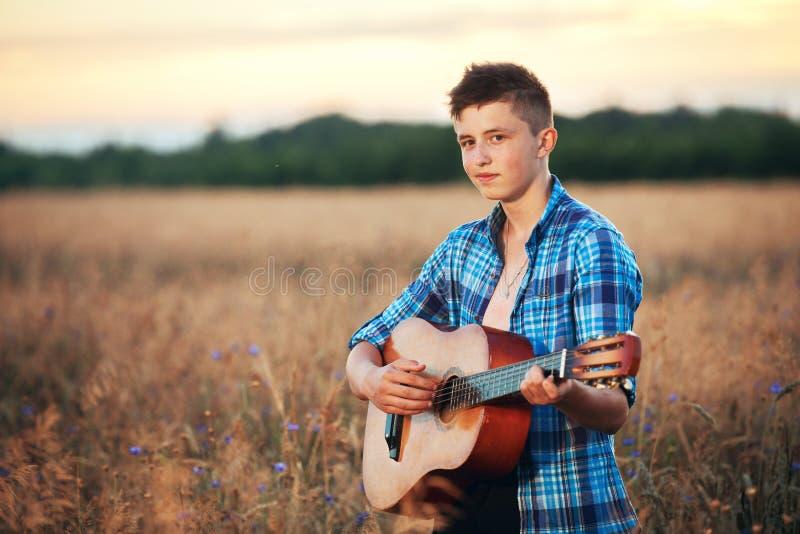 Grabb med en gitarr som spelar sånger på solnedgångnaturen royaltyfri foto
