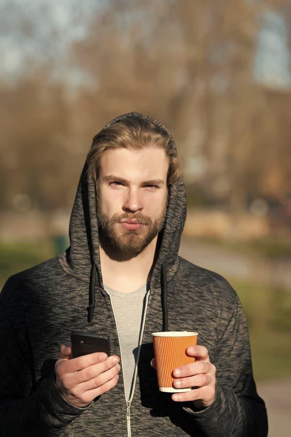 Grabb med smartphonen och den takeaway drinken på ny luft Skäggig man i kopp för kaffe för huvhåll disponibel på soligt utomhus- royaltyfri bild