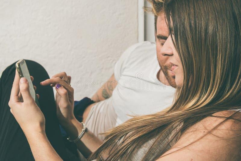 Grabb och en flicka som håller ögonen på mobiltelefonsammanträdet på en soffa royaltyfri fotografi