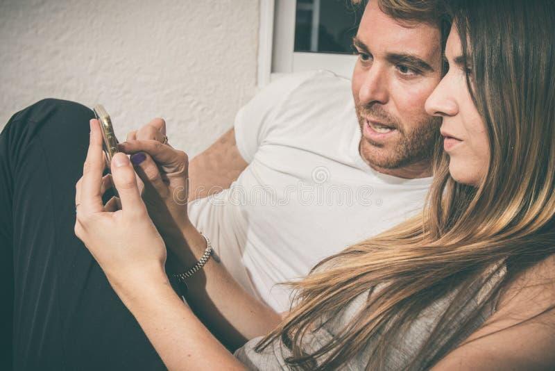Grabb och en flicka som håller ögonen på mobiltelefonsammanträdet på en soffa fotografering för bildbyråer