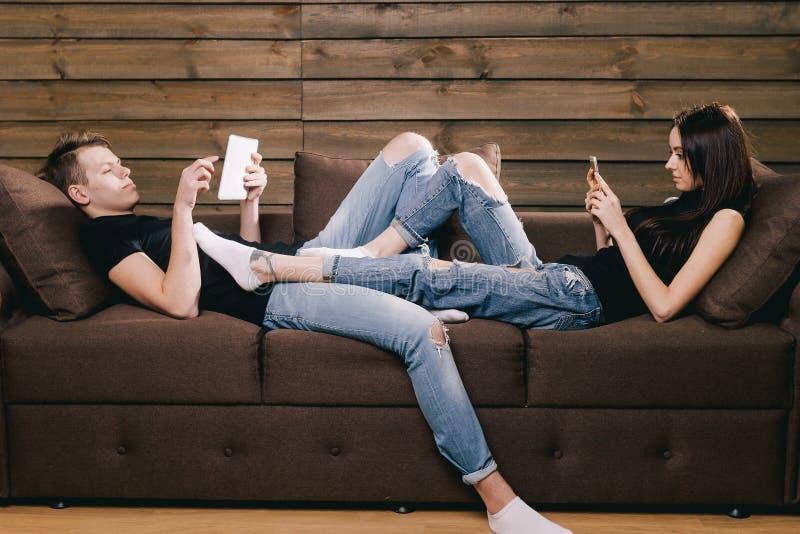 Grabb och flicka som använder telefonen och minnestavlan arkivbild