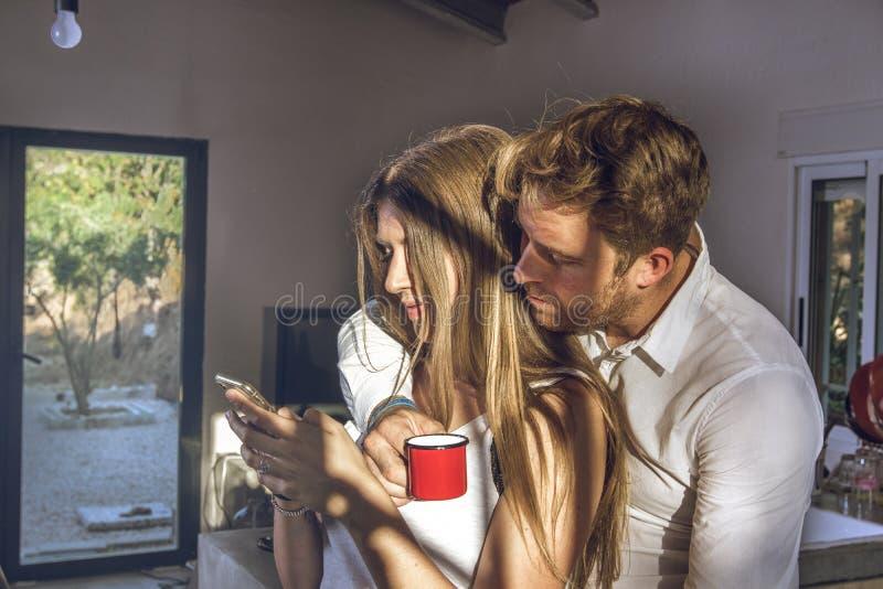 Grabb och flicka som hemma ser deras mobiltelefoner Par av grabben och flickan som ser deras mobiltelefon royaltyfri fotografi