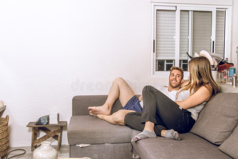 Grabb och flicka som kopplas av och hemma les på soffan arkivfoton