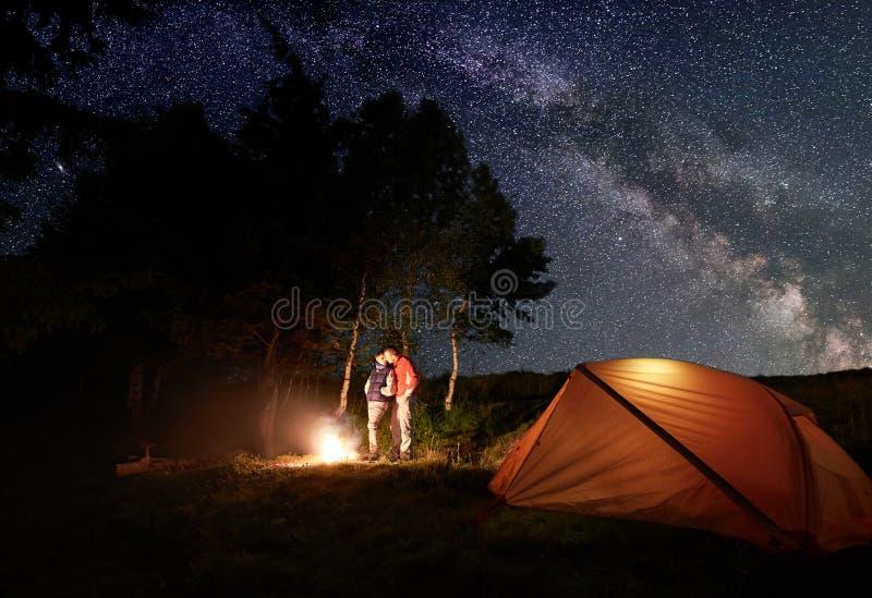 Grabb och flicka som kysser vid branden under ljus stjärnklar himmel som är den synliga mjölkaktiga vägen nära tältet i trän fotografering för bildbyråer