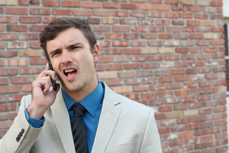 Grabb på telefonen med huvudvärk Uppriven olycklig man som talar på telefonen på bakgrund för tegelstenvägg Negativa mänskliga si fotografering för bildbyråer