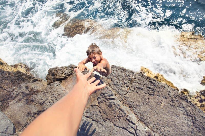 Grabb som frågar för hjälp till någon att klättra en klippa fotografering för bildbyråer