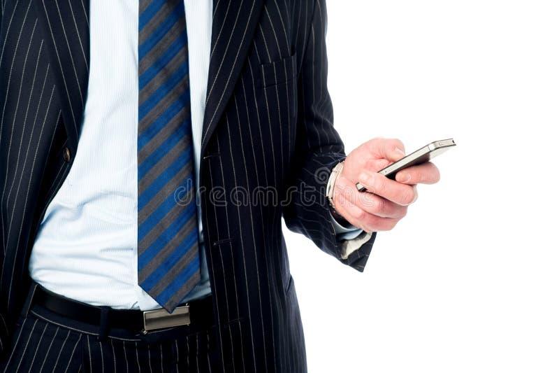 Grabb som fungerar hans mobiltelefon royaltyfria bilder