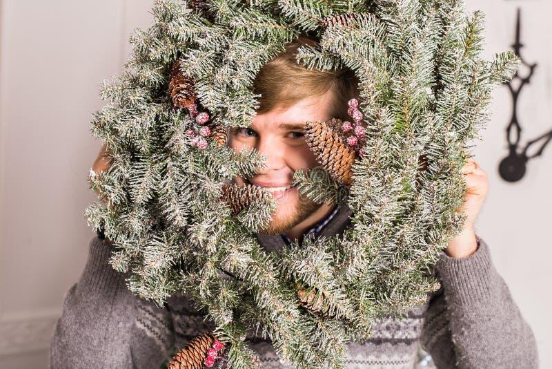 Grabb som har gyckel på partiet Man med en julkrans på hans framsidabegrepp av ett roligt parti på jul eller det nya året royaltyfri foto