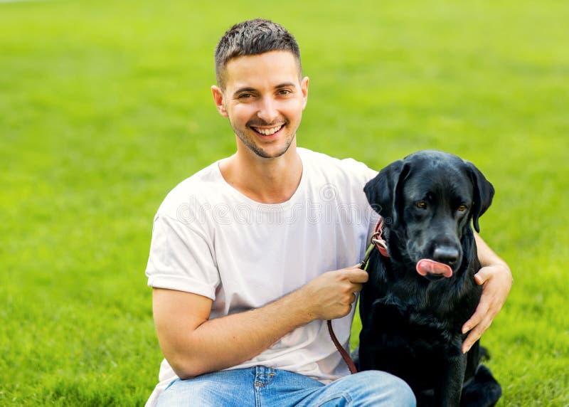 Grabb som kramar med hans hund labrador som spelar i parkera royaltyfri fotografi